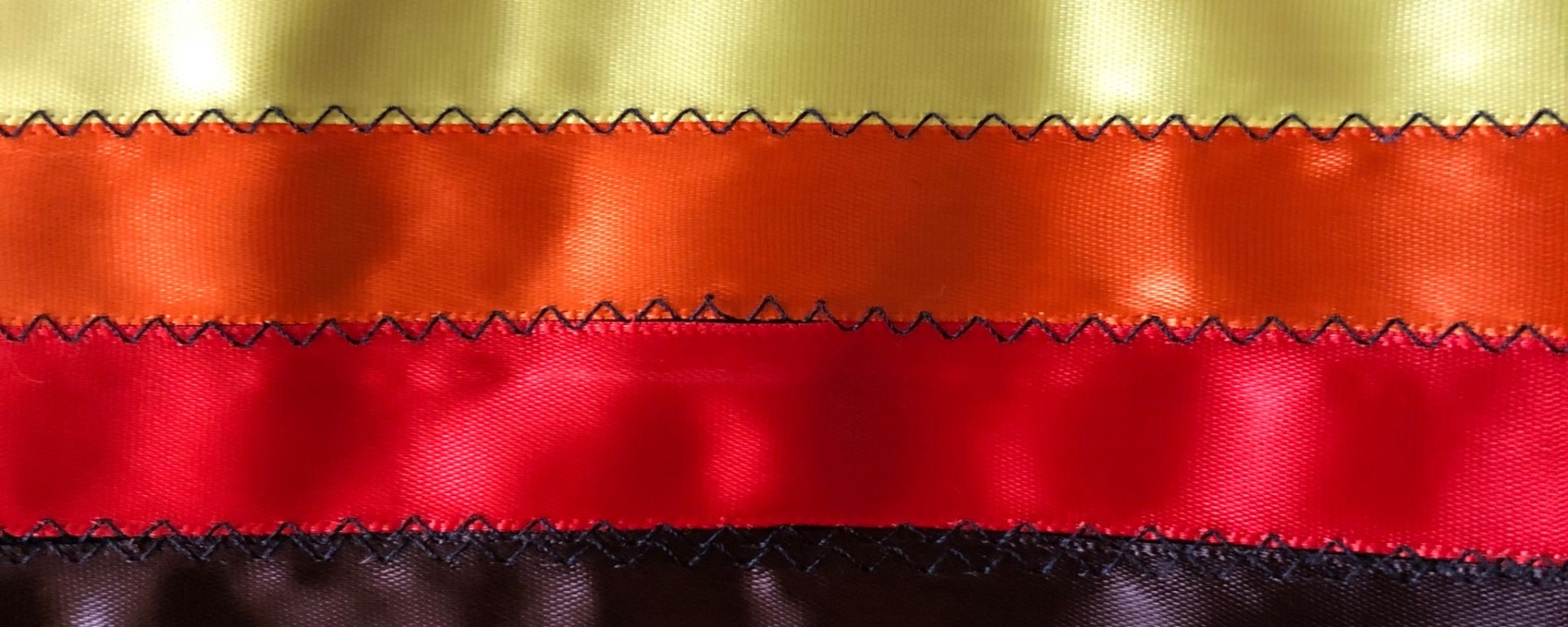 A photo of black, yellow, orange, and red ribbons sewn together