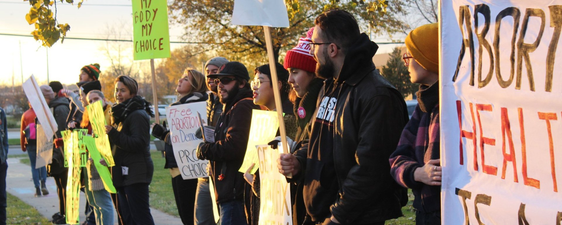 A picture of people standing in a line, holding signs in support of abortion rights, while the sun sets.